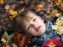 Retrato de la muchacha hermosa en hojas de otoño Imagen de archivo
