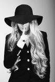 Retrato de la muchacha hermosa en sombrero en perfil, presentando en estudio, fotografía blanco y negro Imágenes de archivo libres de regalías