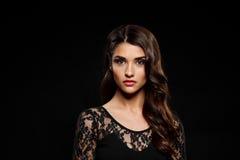 Retrato de la muchacha hermosa en vestido negro sobre fondo oscuro Foto de archivo