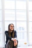 Retrato de la muchacha hermosa joven del estudiante en vidrios en el alféizar blanco Fotografía de archivo libre de regalías