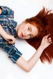 Retrato de la muchacha hermosa joven del jengibre lauing abajo sobre el fondo blanco Imágenes de archivo libres de regalías