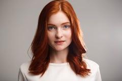 Retrato de la muchacha hermosa joven del jengibre sobre fondo gris con la luz trasera Fotos de archivo