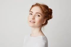 Retrato de la muchacha hermosa joven del pelirrojo con las pecas que miran la cámara que sonríe sobre el fondo blanco Foto de archivo libre de regalías