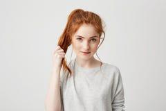 Retrato de la muchacha hermosa joven del pelirrojo que toca su cola del pelo que mira la cámara sobre el fondo blanco Imagen de archivo