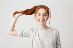 Retrato de la muchacha hermosa joven del pelirrojo que toca su cola del pelo que mira la cámara sobre el fondo blanco Fotos de archivo libres de regalías