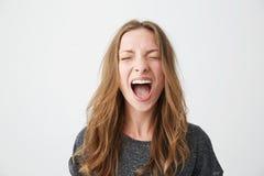Retrato de la muchacha hermosa joven emotiva que grita con los ojos cerrados sobre el fondo blanco Foto de archivo