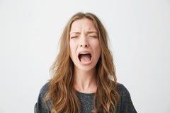 Retrato de la muchacha hermosa joven emotiva que grita con los ojos cerrados sobre el fondo blanco Imagenes de archivo