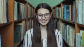Retrato de la muchacha hermosa joven en biblioteca Estudiante que estudia entre la porción de libros entre los shelfs almacen de video
