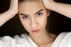 Retrato de la muchacha hermosa joven de los marrón-ojos con el maquillaje natural que lleva a cabo sus manos en su cabeza imagenes de archivo