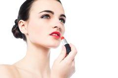 Retrato de la muchacha hermosa que aplica el lápiz labial Imagen de archivo libre de regalías