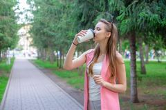 Retrato de la muchacha hermosa que camina en el parque Mantener la bebida para llevar una mano Fotos de archivo libres de regalías