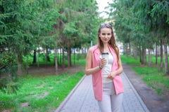 Retrato de la muchacha hermosa que camina en el parque Mantener la bebida para llevar una mano Imagen de archivo