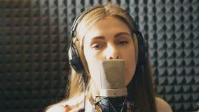 Retrato de la muchacha hermosa que canta en estudio de los sonidos Cantante joven que registra emocionalmente la nueva canción La almacen de metraje de vídeo