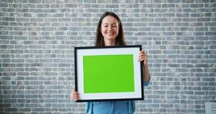 Retrato de la muchacha hermosa que celebra la imagen y la sonrisa dominantes de la maqueta de la croma verde metrajes