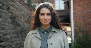 Retrato de la muchacha hermosa que es situación entonces sonriente seria al aire libre en ciudad almacen de video