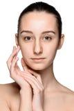 Retrato de la muchacha hermosa que frota ligeramente su cara con Imágenes de archivo libres de regalías