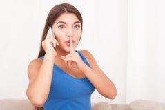 Retrato de la muchacha hermosa que habla por el teléfono en sala de estar Fotografía de archivo libre de regalías