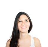 Retrato de la muchacha hermosa que piensa y que mira para arriba contra blanco Foto de archivo libre de regalías