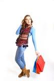 Retrato de la muchacha hermosa que presenta con los bolsos de compras aislados encendido Fotos de archivo libres de regalías