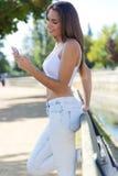 Retrato de la muchacha hermosa que usa su teléfono móvil en ciudad Imágenes de archivo libres de regalías