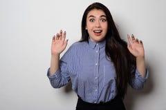 Retrato de la muchacha hermosa sorprendida en ropa de sport con los brazos levantados Imagen de archivo