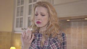 Retrato de la muchacha hermosa trastornada que come una torta dulce en la cocina en casa almacen de video