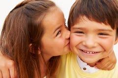 Retrato de la muchacha hispánica que besa al muchacho Imagen de archivo libre de regalías