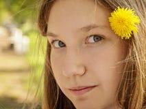 Retrato de la muchacha joven del adolescente en parque con el diente de león en pelo Fotografía de archivo
