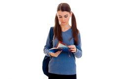 Retrato de la muchacha joven del estudiante del cutie con la mochila y los cuadernos aislados en el fondo blanco Imágenes de archivo libres de regalías
