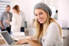 Retrato de la muchacha joven del estudiante que trabaja en el ordenador portátil Foto de archivo libre de regalías