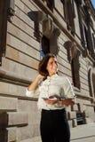 Retrato de la muchacha joven y bonita que usa su teléfono móvil mientras que da un paseo en el ambiente urbano en día soleado Fotos de archivo