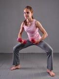 Retrato de la muchacha juguetona de la edad adolescente que ejercita con pesas de gimnasia Imágenes de archivo libres de regalías