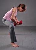 Retrato de la muchacha juguetona de la edad adolescente que ejercita con pesas de gimnasia Imagen de archivo