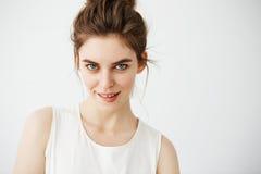 Retrato de la muchacha juguetona hermosa joven con el bollo que mira el labio penetrante de la cámara que presenta sobre el fondo Foto de archivo libre de regalías
