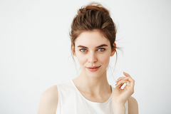 Retrato de la muchacha juguetona hermosa joven con el bollo que mira la cámara que presenta sobre el fondo blanco Fotografía de archivo
