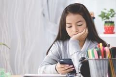 Retrato de la muchacha linda asiática que sostiene el teléfono móvil Imagen de archivo libre de regalías