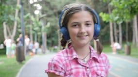 Retrato de la muchacha linda con los auriculares azules que patina en el parque metrajes