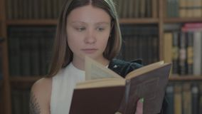 Retrato de la muchacha linda con un tatuaje en el libro de lectura del hombro en el cierre de la biblioteca para arriba Chica jov almacen de video