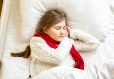 Retrato de la muchacha linda en bufanda y suéter que duerme en la cama Fotos de archivo