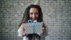 Retrato de la muchacha linda en caja de regalo de ofrecimiento del sombrero del partido que sonríe mirando la cámara almacen de metraje de vídeo