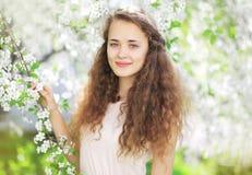 Retrato de la muchacha linda en el jardín floreciente de la primavera Foto de archivo