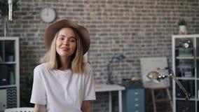 Retrato de la muchacha linda en la situación del sombrero en oficina solamente que sonríe mirando la cámara almacen de video