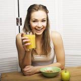 Retrato de la muchacha linda feliz con el desayuno, la manzana verde y el zumo de naranja Fotografía de archivo libre de regalías