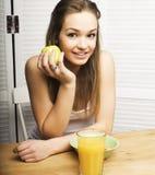 Retrato de la muchacha linda feliz con el desayuno, la manzana verde y el zumo de naranja Imágenes de archivo libres de regalías