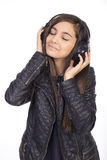 Retrato de la muchacha linda feliz con música que escucha de los auriculares Foto de archivo