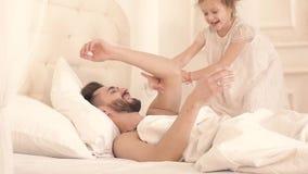Retrato de la muchacha linda que despierta a su padre hasta abrazo y juego almacen de metraje de vídeo