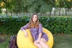 Retrato de la muchacha linda que se sienta en silla y que sonríe en fotografía Fotografía de archivo libre de regalías