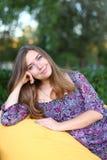 Retrato de la muchacha linda que se sienta en silla y que sonríe en fotografía Imagen de archivo libre de regalías