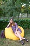 Retrato de la muchacha linda que se sienta en silla y que sonríe en fotografía Fotos de archivo