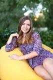 Retrato de la muchacha linda que se sienta en silla y que sonríe en fotografía Foto de archivo libre de regalías